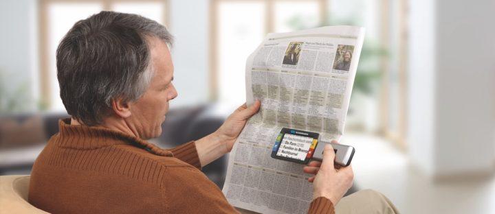 Makuladegeneration – Mann liest Zeitung mit Lupe